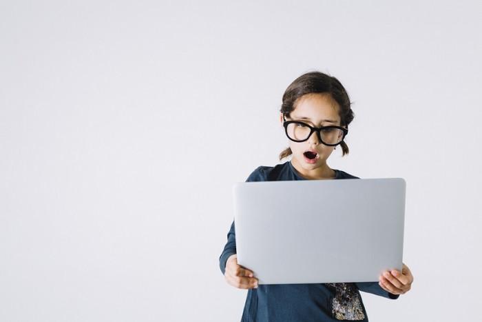 Dziewczynka w za dużych okularach na tle szarej ściany trzyma laptop z zdziwionym wyrazem twarzy