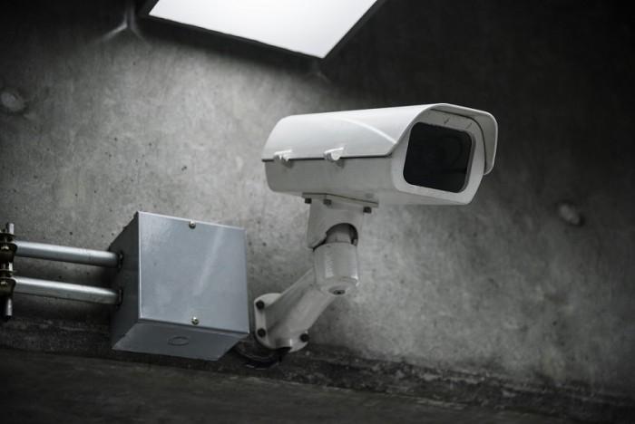 Kamera monitoringu na betonowej ścianie, pod lampom, obok metalowej puszki na elektronikę