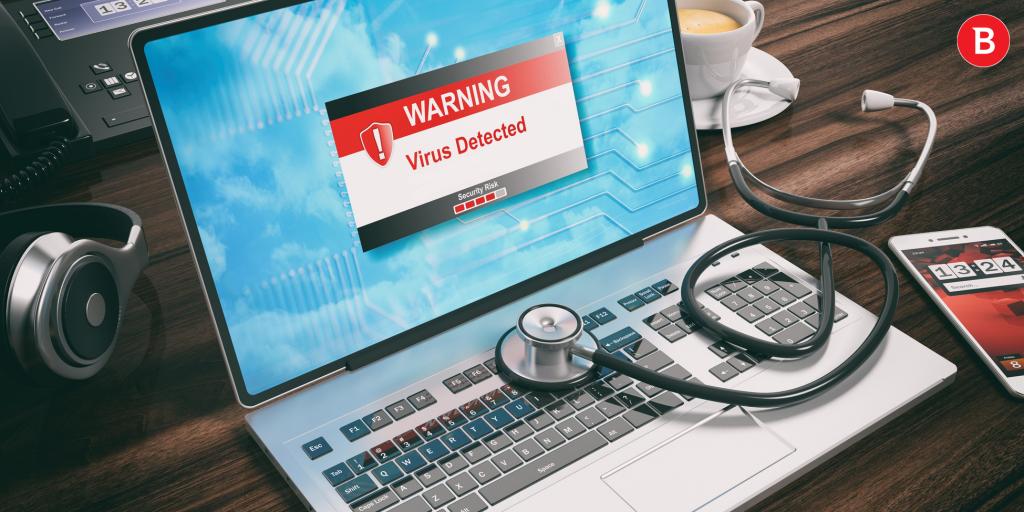 Laptop z stetoskopem na klawiaturze, z wyświetlonym na ekranie ostrzeżeniem o wykryciu wirusa