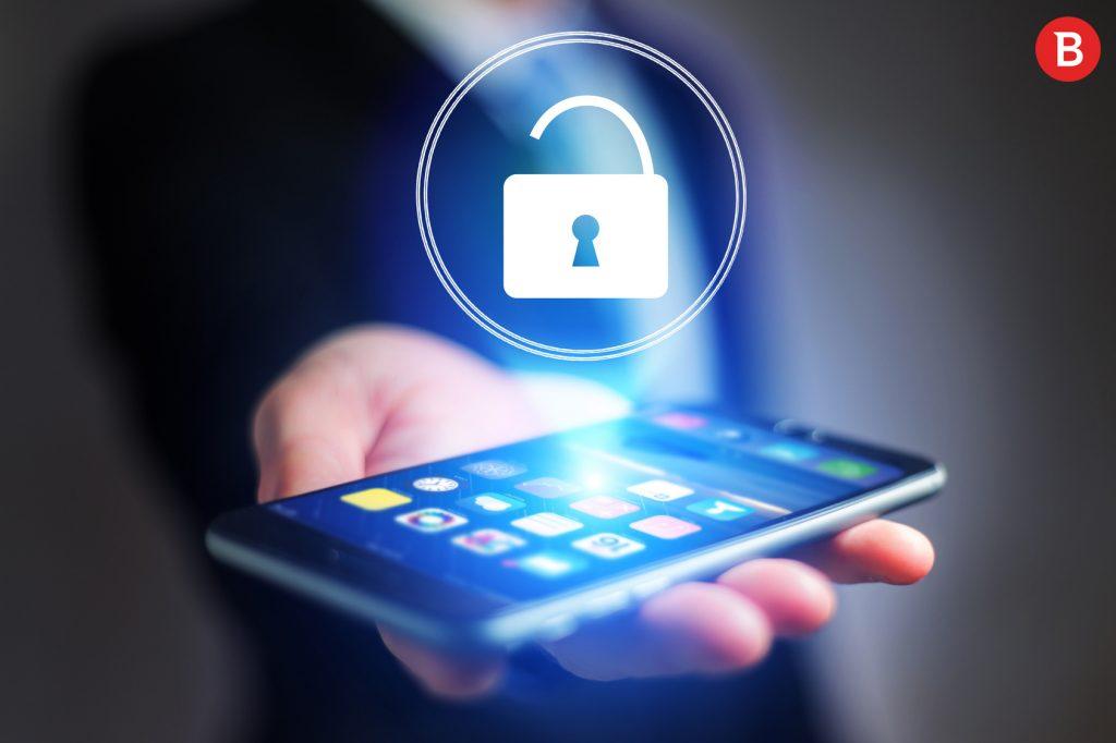 Smartfon, trzymany na dłoni przez mężczyznę w garniturze, wyświetlający hologram otwartej kłódki w pierścieniu