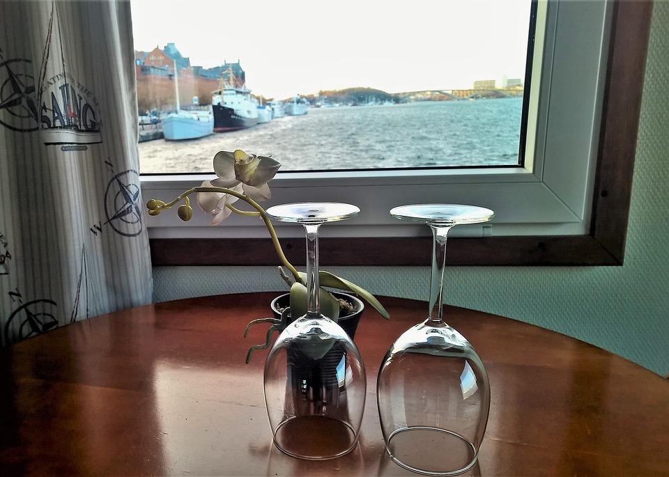 Dwie lampki do wina odwrócone do góry stopką stojące na polakierowanym drewnianym stole, obok kwiatka w doniczce na tle okna z widokiem na szeroką rzekę, statki i most