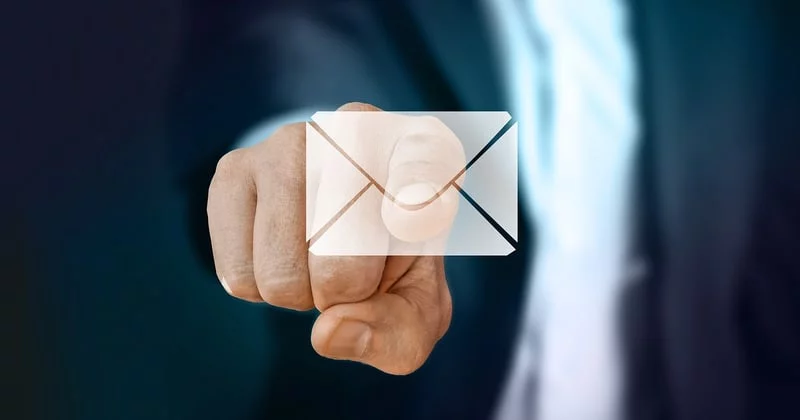 """Mężczyzna z wyciągniętą prawą ręką w stronę użytkownika """"dotyka"""" palcem wskazującym symbol koperty"""