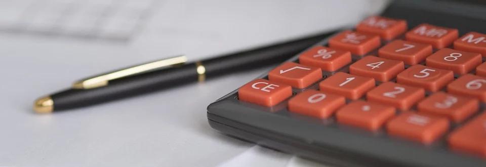 Ciemno szary kalkulator z czerwonymi przyciskami i czarno złoty cienki długopis położne na dokumentach