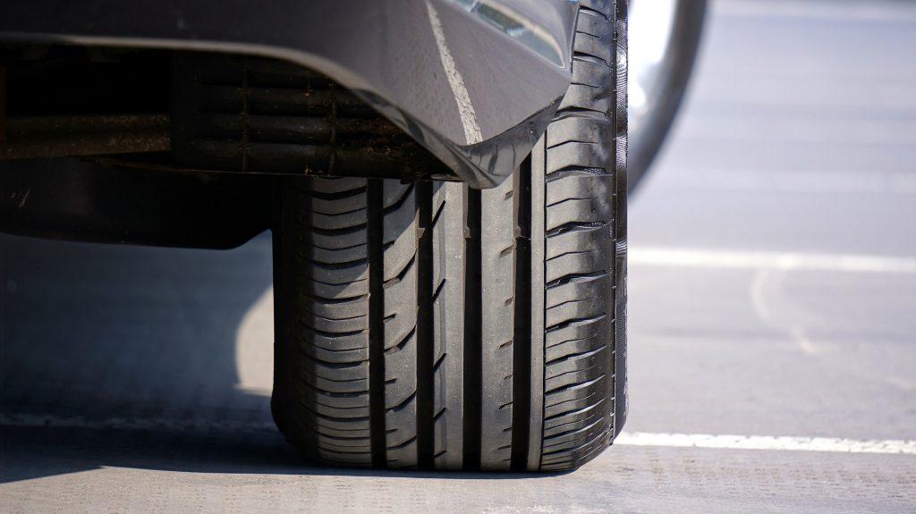 Zbliżenie na tylną oponę samochodu z asymetrycznym bieżnikiem