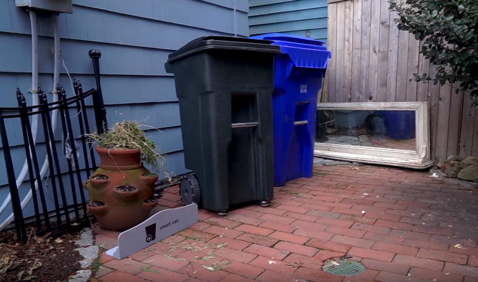 Dwa kosze na śmieci jeden czarny drugi niebieski stojące na podwórku obok domu pomiędzy starym lustrem leżącym na ziemi a donicą, częścią płotu i tabliczki z napisem smart can