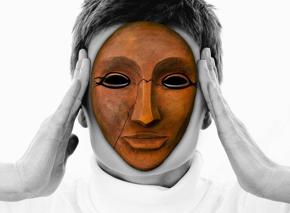 Gliniana popękana maska z namalowanymi konturami wokół oczu konturami na twarzy człowieka, który trzyma się z skronie.