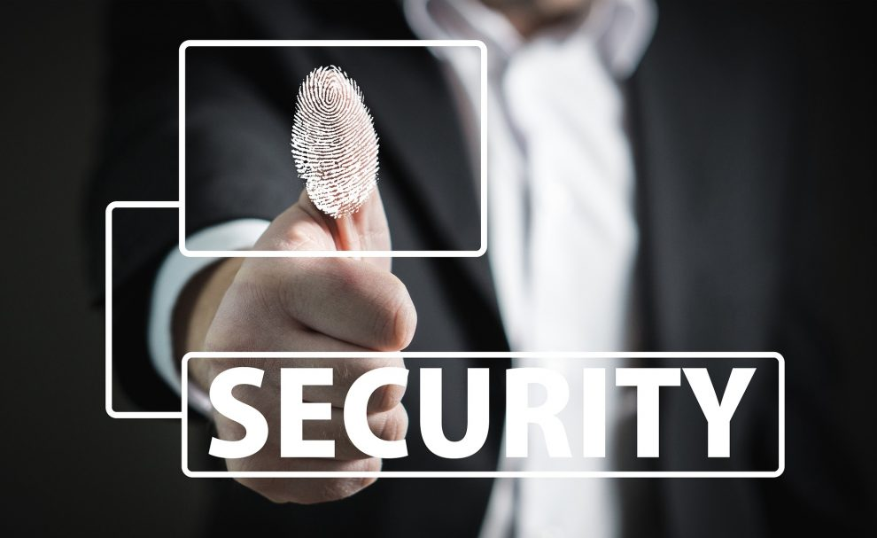 Mężczyzna w garniturze z wyciągnięta do przodu ręką i wystawionym kciukiem ku górze, z grafiką linii papilarnych na nim, i napis security