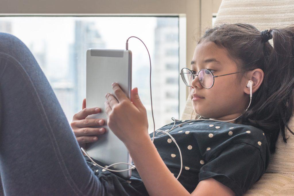 Dziewczynka leżąca przy oknie oglądająca film na tablecie z podłączonymi do niego słuchawkami dousznymi
