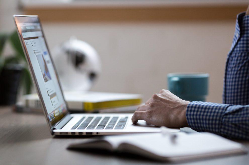 Mężczyzna w koszuli w niebiesko białą kratkę pracujący na laptopie