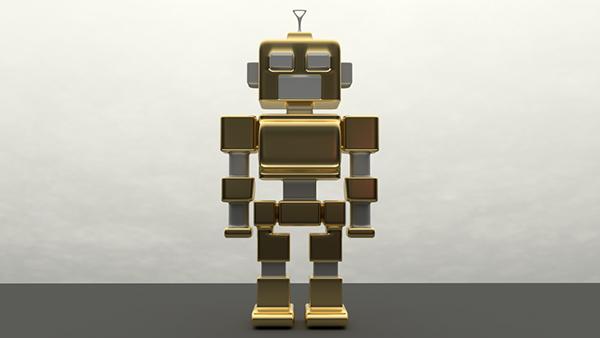 Figurka małego, złoto-srebrnego, robot z antenką na głowie, stojący na szarym blacie na tle białej ściany