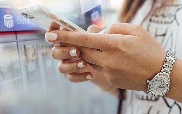 Kobieta z telfonem w rękach na tle banku PKO BP